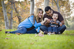 Couple with a baby sitting in a grassy field blowing bubbles and smiling.