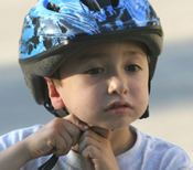 Photo of a child putting on a bicycle helmet.
